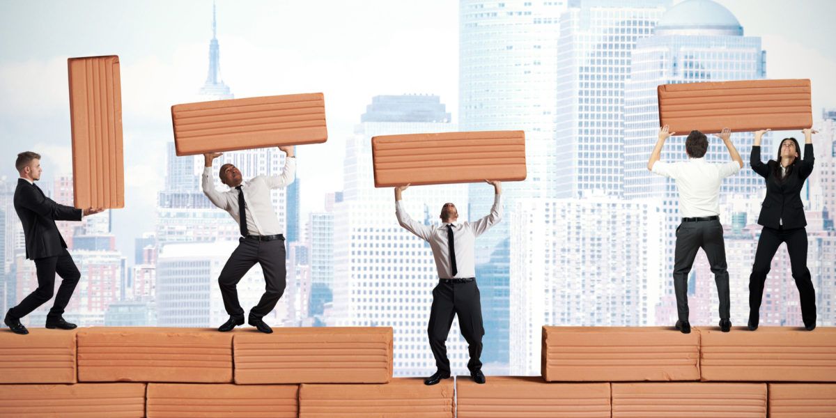 businessmen building with life-sized blocks