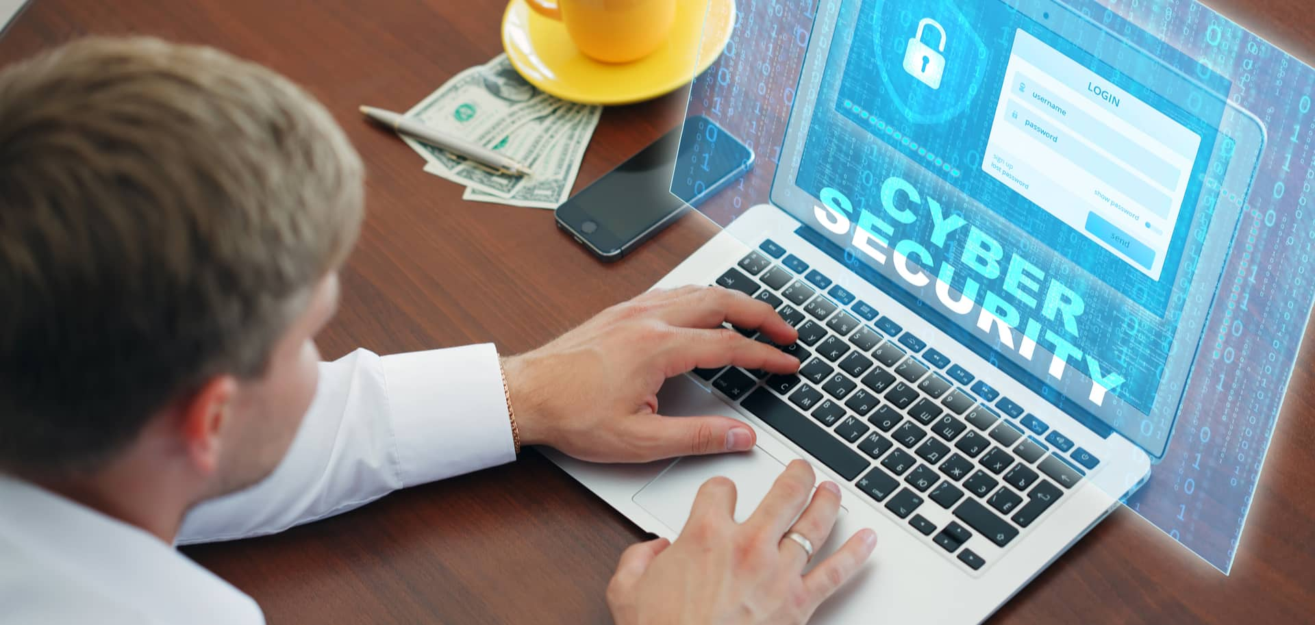 Man working on computer with cyber security image and dollar bills under his coffee mug
