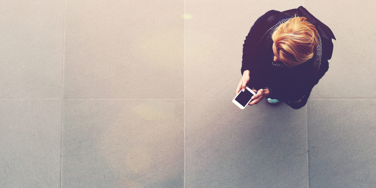 woman looks at cell phone