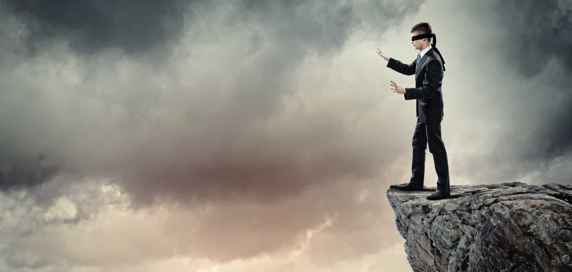 Man with blindfold stands on edge of cliff